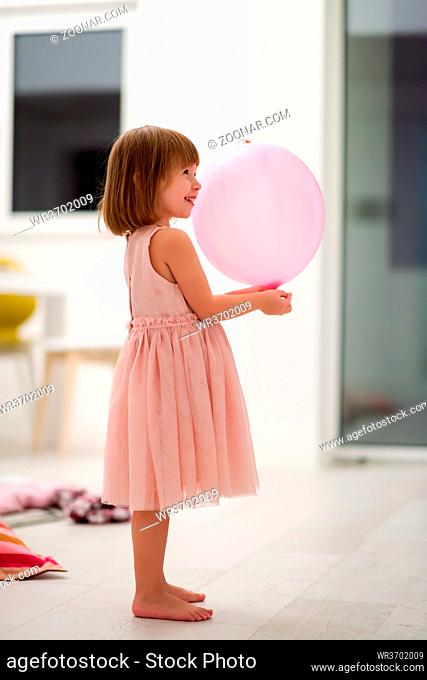happy cute little girl in a pink dress enjoying while playing with balloons on beautiful evening near the window at home