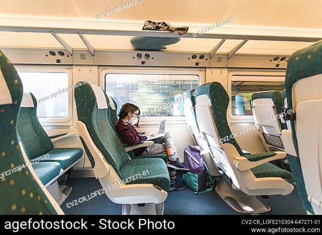 Wide view of seats and boy wearing mask uses laptop traveling by train