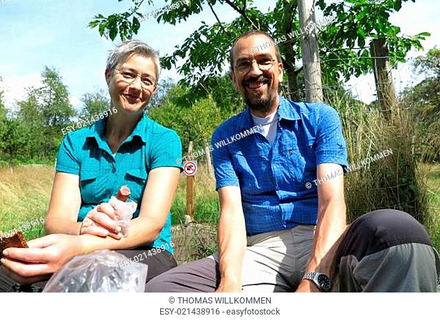 Couple of happy hikers having a picnic in a fruit orchard in the Odenwald hills near Fränkisch-Crumbach and Eberbach