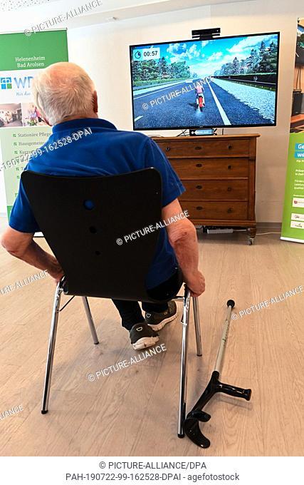 22 July 2019, Hessen, Bad Arolsen: Resident Gustav Vering (89) tries his hand at motorcycling at the Helenenheim Bad Arolsen game console