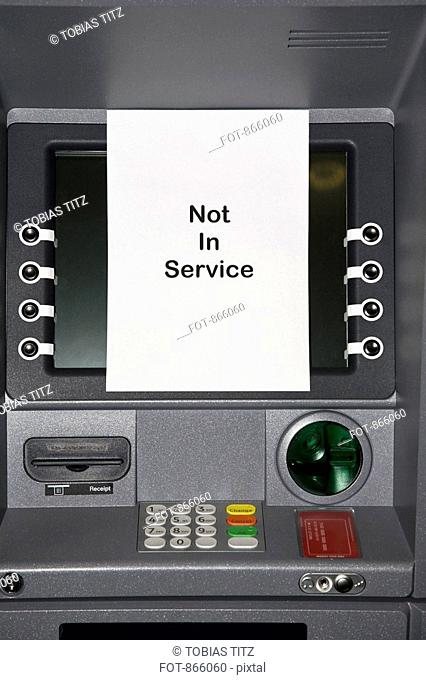 An ATM with a sign stating NOT IN SERVICE