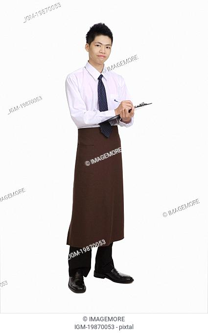 Young waiter writing on the clipboard and looking at the camera