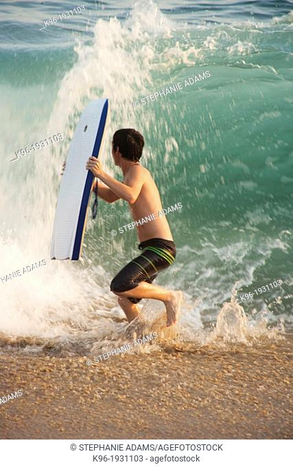 boy running from a big ocean wave