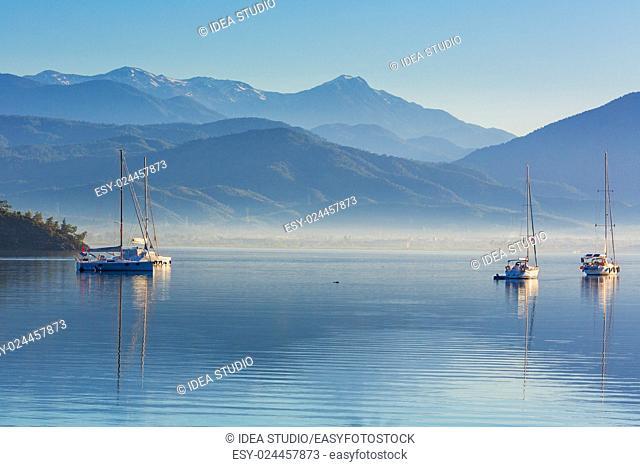 Anchored yachts at misty morning on the lake on mountains background, Fethiye, Mugla Province, Turkey