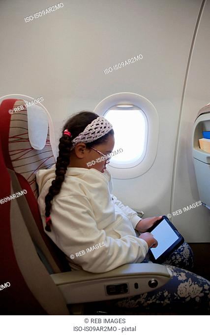 Young girl sitting in seat on aeroplane using digital tablet