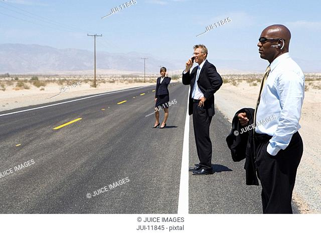 Businessmen and woman on open road in desert using mobile phones, side view