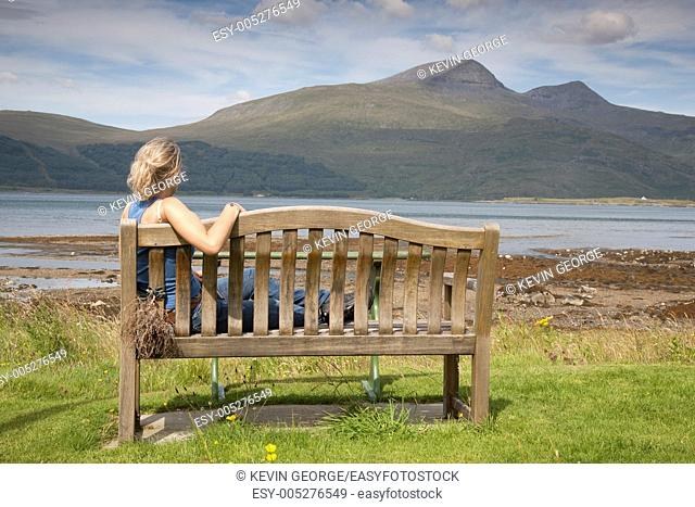 Young Woman sitting on Bench on Isle of Mull, Scotland