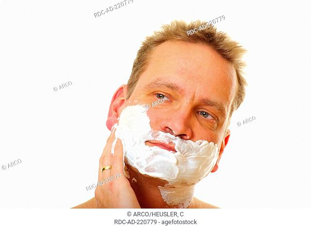 Man with shaving foam in his face, shaving