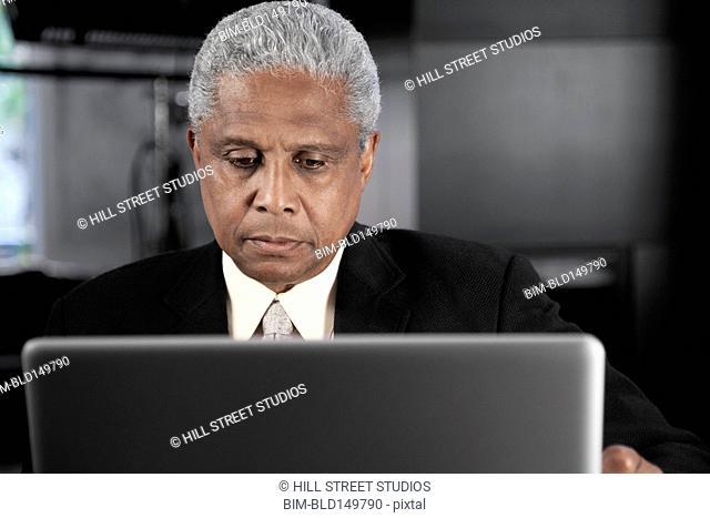 Serious Black businessman using laptop