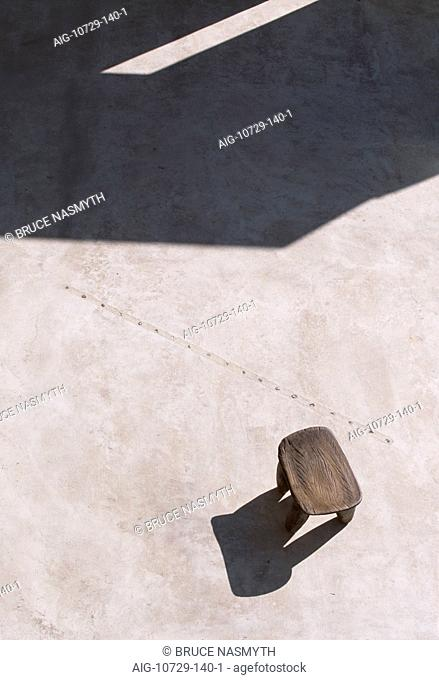 Modern concrete patio with African stool, shadows and line of Feng Shui crystals