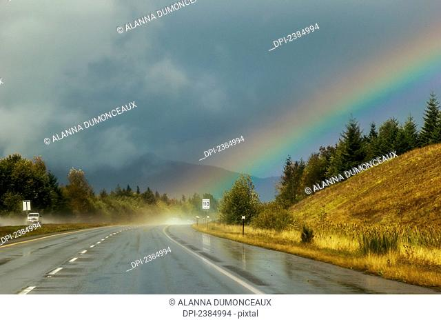 A rainbow comes from the storm clouds right onto the highway ahead; Parksville, British Columbia, Canada