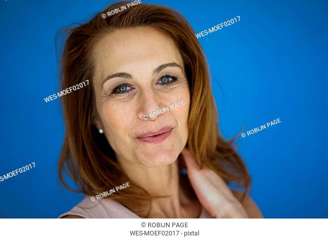 Redheaded businesswoman against blue background, portrait