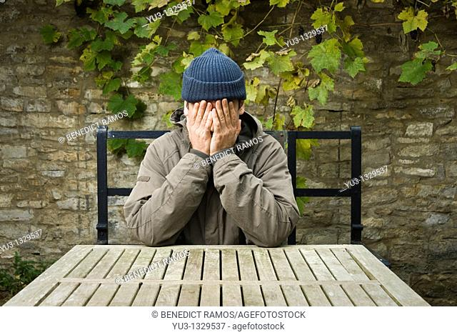Man sitting at table in courtyard with his hands concealing his face