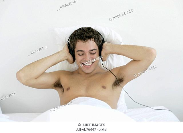 Portrait of a young man wearing headphones in bed