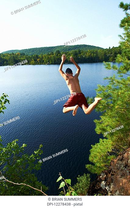 Boy jumping into lake off a cliff; Lac des Neiges, Quebec, Canada