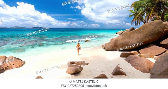 Active sporty woman wearing stylish bikini enjoying swimming and snorkeling at amazing on Anse Patates beach on La Digue Island, Seychelles