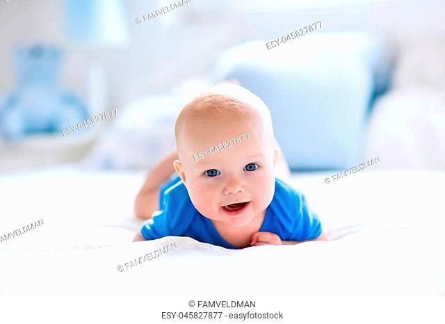 Adorable baby boy in white sunny bedroom. Newborn child relaxing in bed. Nursery for young children. Textile and bedding for kids