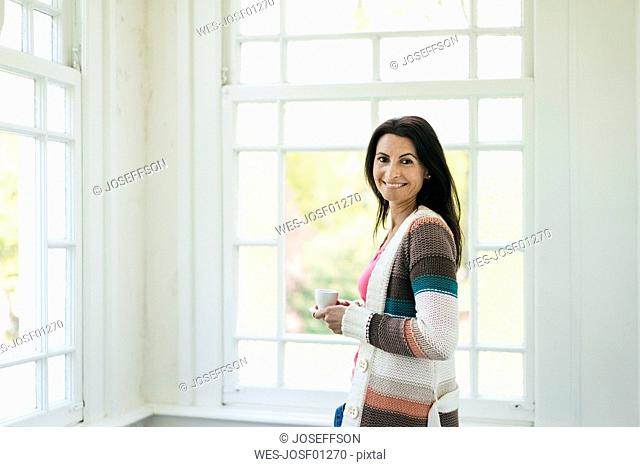 Portrait of smiling woman at the window