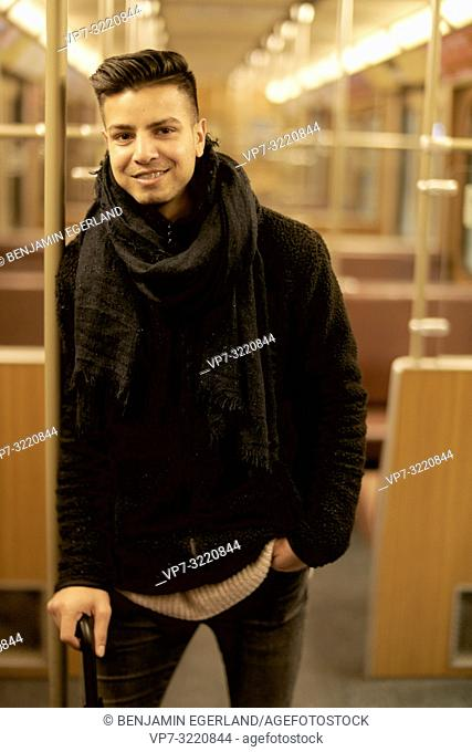 young man, Afghan ethnicity, standing in underground train, public transportation