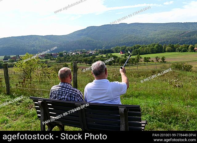 15 September 2020, Hessen, Heldra: Werner Jung (l) and Hubert Steube sit on a bench above Heldra and look together at the Heldrastein