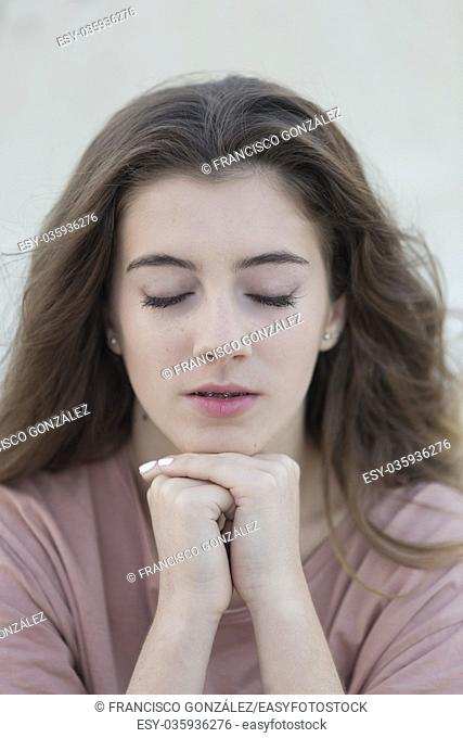 Close-up portrait of a teenage woman with closed eyes. Shot with natural light