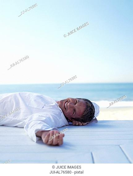 Portrait of a young man lying on a deck beside the beach