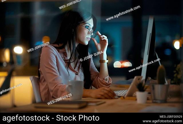 Young woman with glasses working at desk in office
