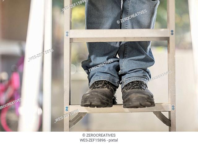 Man standing on ladder, partial view