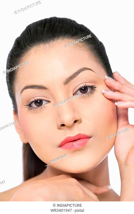 Pretty young woman touching her face over white background