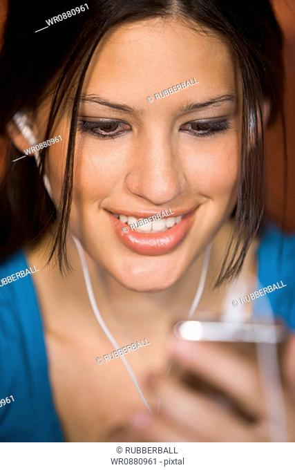 Close-up of a young woman holding MP3 Player and listening to music
