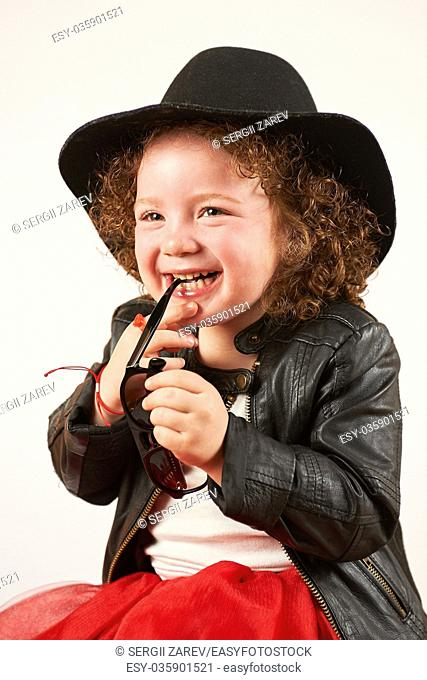 Little girl with black hat sitting and laughing