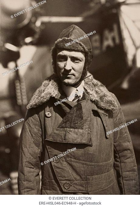 Arctic aviator Richard Byrd in fur lines leather flight suit and hat. In the background is his Fokker Tri-motor monoplane in which he flew over North Polar...