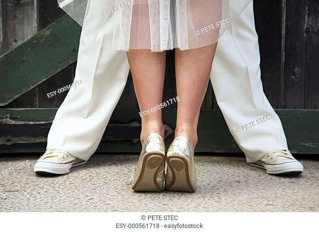 a bride standing on her tip toes in front of a groom