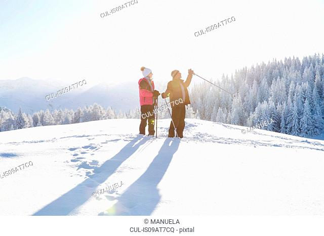 Senior couple on snow covered landscape holding walking poles looking away, Sattelbergalm, Tyrol, Austria
