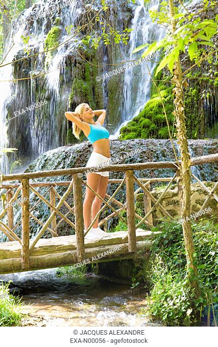 Young woman exercising with waterfall in background, Monasterio de Piedra; Zaragoza; Aragon; Spain;