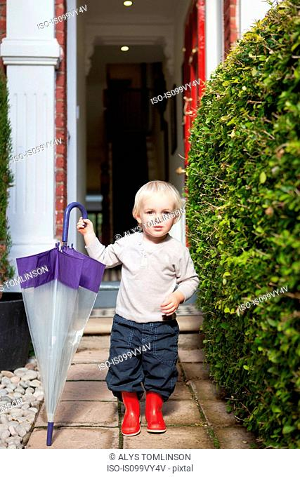 Little boy standing on front garden path with umbrella and rubber boots