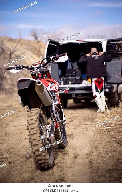 Close up of motorcycle behind dirt bike rider and van