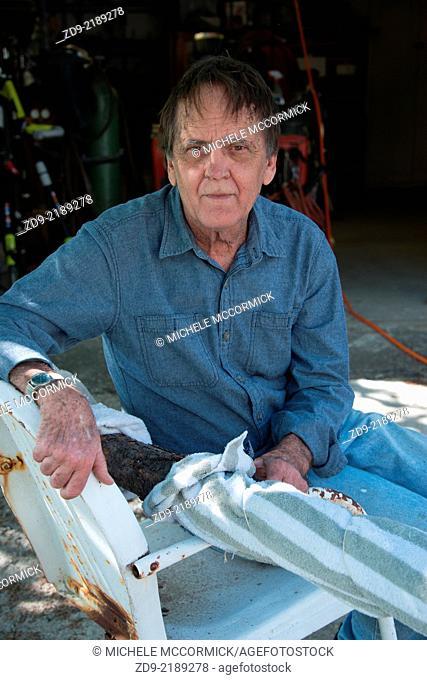 An older man pauses at his workshop