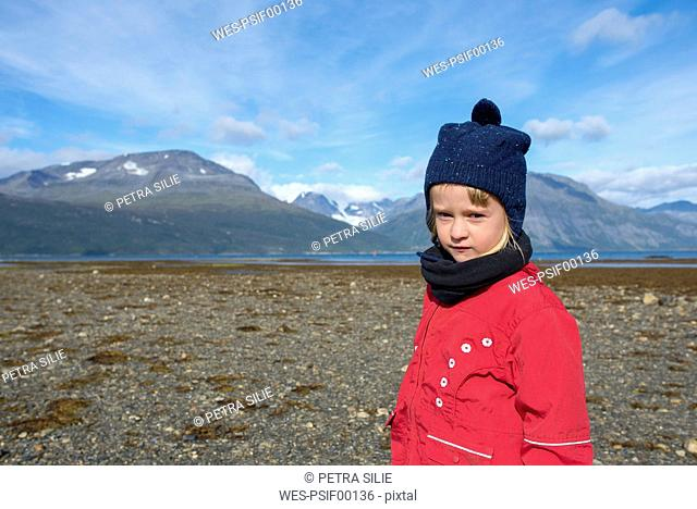 Norway, girl wearing bobble hat and red jacket at the beach, Lyngen fjord