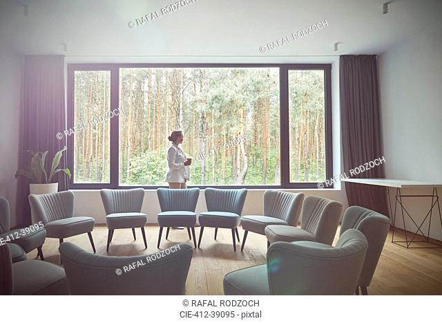 Pensive woman looking out windows at tress in group therapy room
