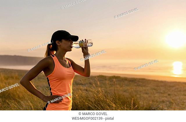 Young athlete woman drinking water at sunset
