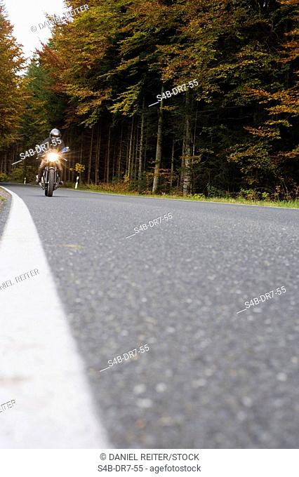Motorcyclist on the street, Bavarian Alpine foothills, Bavaria, Germany