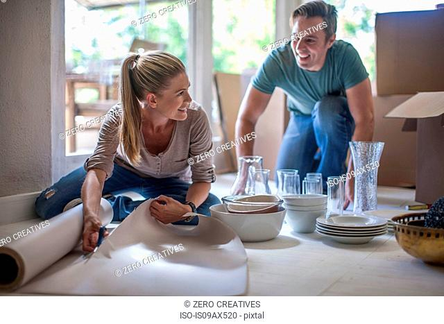Moving house: couple preparing to pack glassware