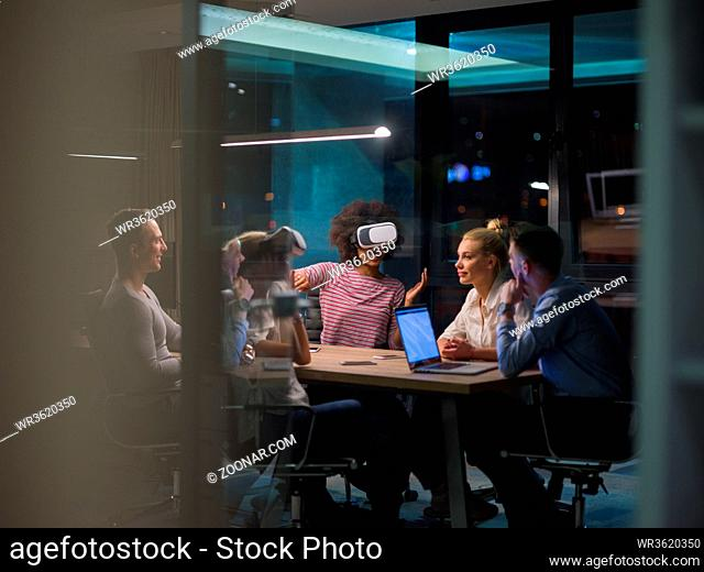 Multiethnic Business team using virtual reality headset in night office meeting Developers meeting with virtual reality simulator around table in creative...