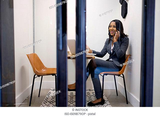 Businesswoman sitting in office using smartphone, laptop on table in front of her