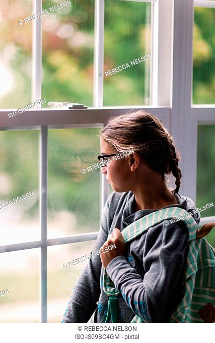 Girl with backpack gazing through house window