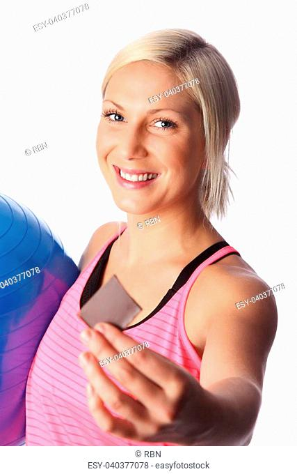 Attractive woman offering you a bite of chocolate after workout! White background