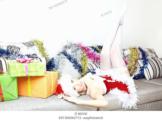 Sensual lady in Santa Claus costume with white housings laying on a sofa near gift boxes