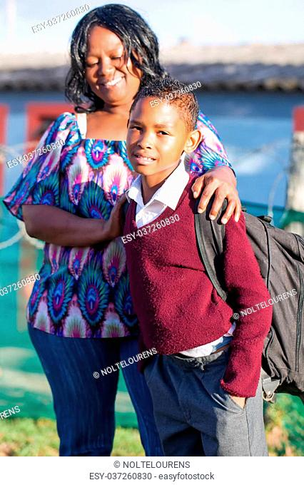 an young african boy in his school clothes standing with his proud mother before heading for school