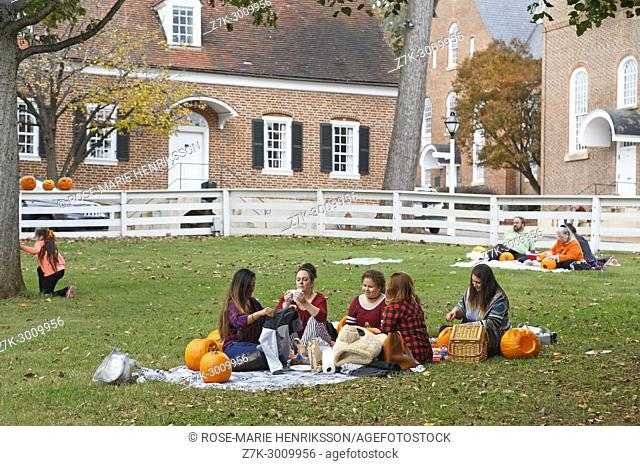 People having picnic and carving pumpkins at the yearly pumpkin carving event in Old Salem